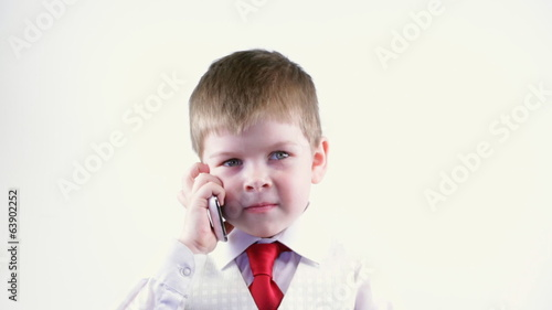 Boy in a business suit talking on the phone