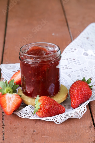 strawberry jam with fresh berries in a jar on the table