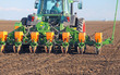 Leinwanddruck Bild - Agricultural tractor sowing and cultivating field