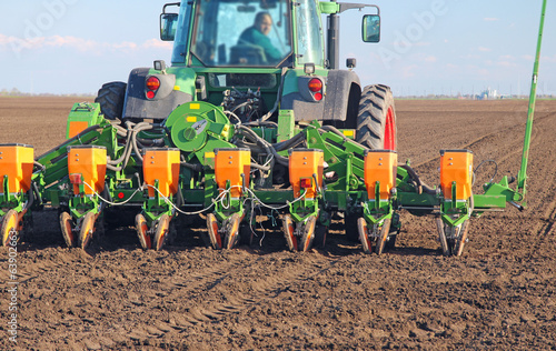Leinwanddruck Bild Agricultural tractor sowing and cultivating field