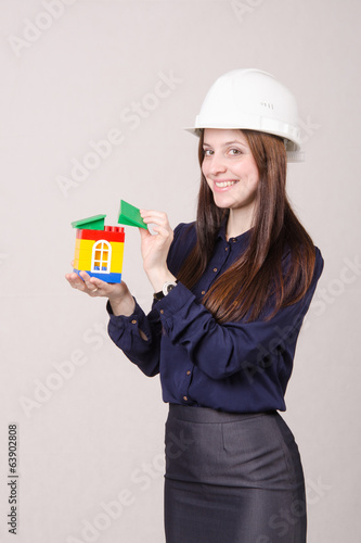 Construction worker stands with a house in the hands of