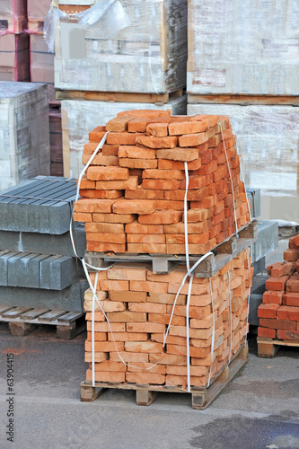 Stack of orange clay brick on pallet