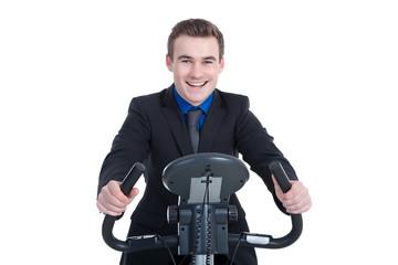 Junger Geschäftsmann lächelt auf Heimtrainer im Job
