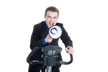 Junger Mann auf Heimtrainer mit Megafon schreit