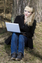 Woman with the laptop sits on a footpath in wood