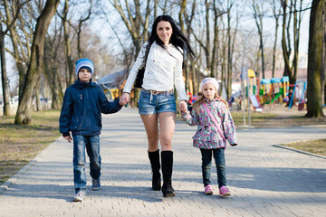 Beautiful mom walking in the park with her son and daughter
