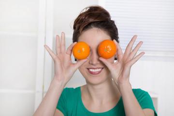 Vitamine - Frau hält sich Mandarinen vor die Augen