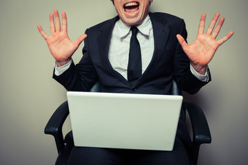 Excited young businessman with laptop