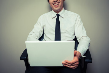 Happy young businessman in office chair