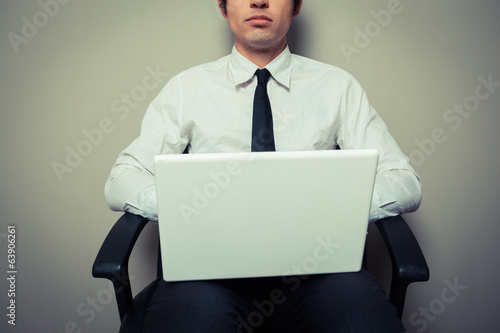 Businessman in office chair working on laptop