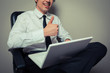 Businessman in office chair giving thumbs up