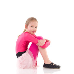 Little girl sitting on the floor, Side view.