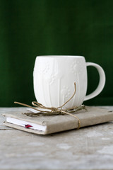 One white cup on a green background and vintage notebook