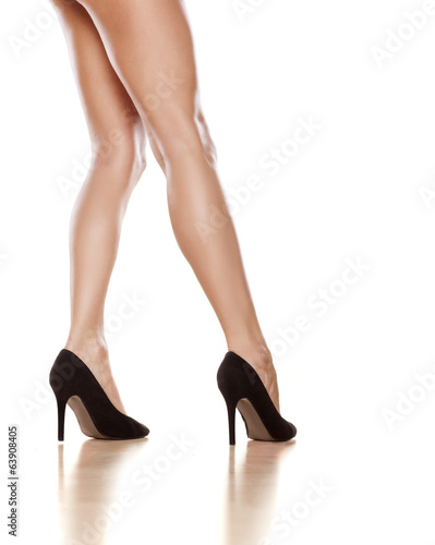 pretty female legs in black shoes with high heels on white