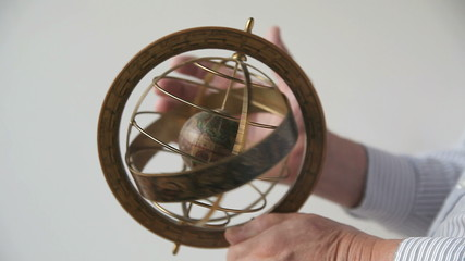 man spins armillary sphere