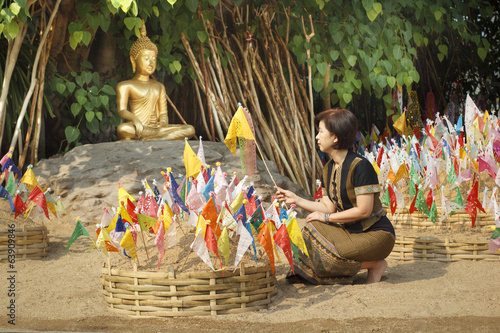 Woman pinned traditional flags on sand pagoda