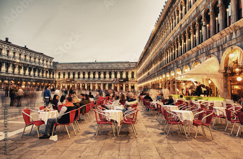 VENICE, ITALY - MAR 23, 2014: Tourists enjoy cafe in Piazza San