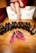 pink sneakers among black high heeled shoes at wardrobe