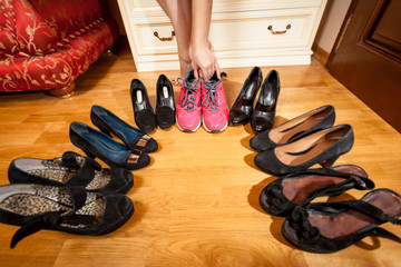 female hand picking sneakers among high heeled shoes