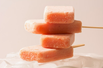 Stacked Fruit Popsicles on Ice with Strawberry, Orange, Pineappl