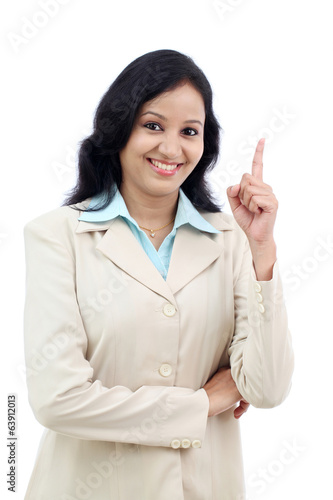 Confident business woman pointing up against white
