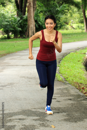 Asian woman running in park