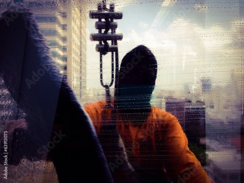 silhouette of a man cleaning office building window