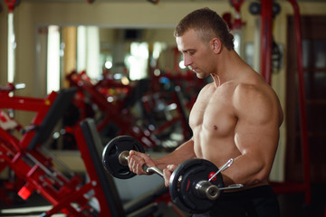 Strong man bodybuilder with dumbbells in a gym