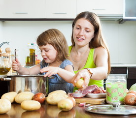 Happy mother with child cooking