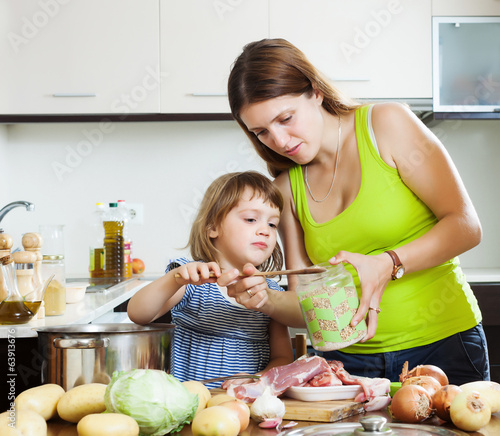 mother with daughter cooking with groats