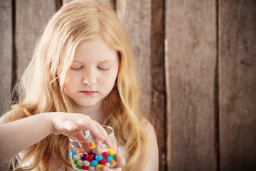 girl with sweet on wooden background