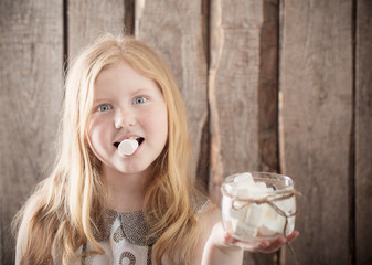 Girl with  marshmallows on wooden background