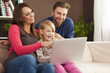 Family laughing together and using laptop at home