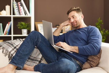 Attractive man using laptop at home