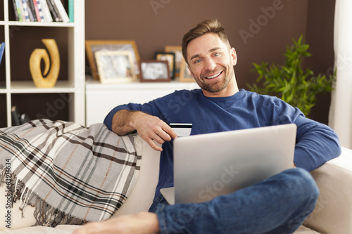 Smiling man with laptop and credit card on sofa
