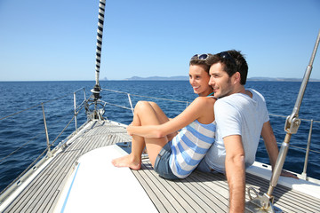 Couple stting on sailboat deck looking at sealine