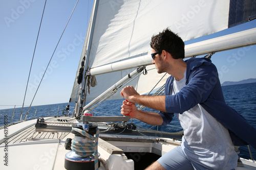 Man sailing with sails out on a sunny day - 63916836