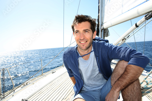 Smiling handsome man on sailboat