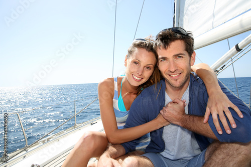 Smiling couple enjoying cruising journey on sailboat