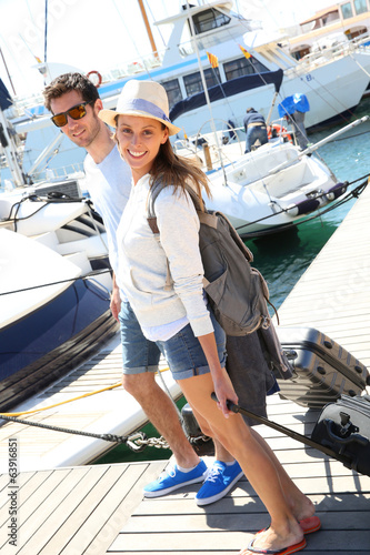 Happy couple getting on board for sailboat cruising