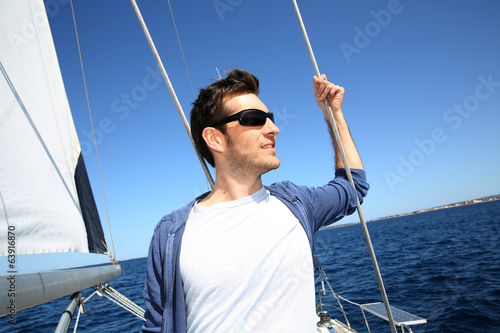 Skipper standing on sailboat while sailing