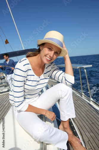 Beautiful woman with hat enjoying cruising on boat