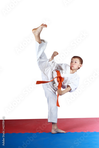Boy in karatege is doing high kick leg