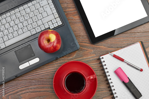 Laptop and office supplies on wooden table