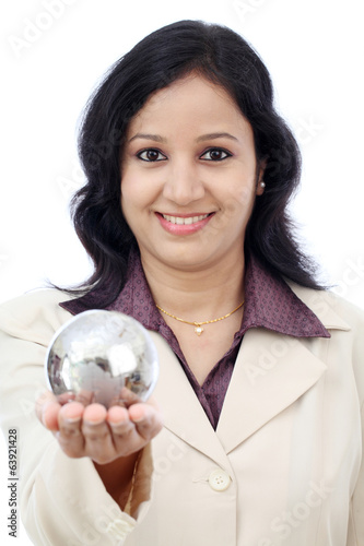 Young Indian business woman holding puzzle globe against white
