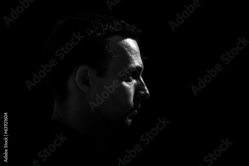 Monochrome profile portrait of young Caucasian man on black back