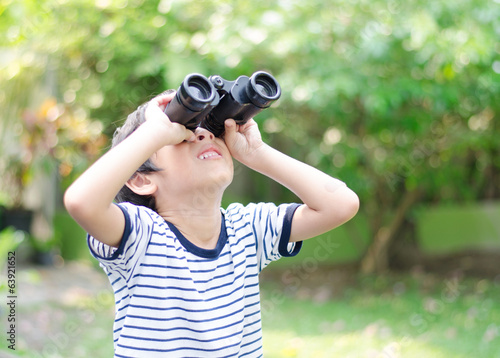 Little boy looking trough a binoculars