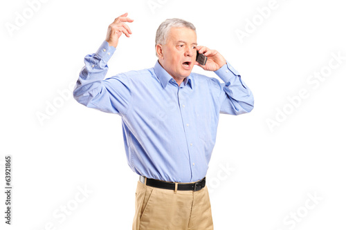Angry mature man talking on the phone