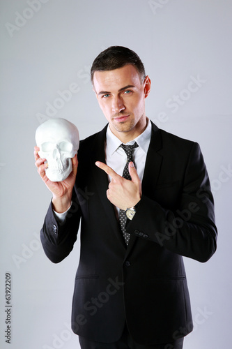 Businessman holding skull and showing on it over gray background
