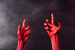 Creepy red devil hands with black sharp nails